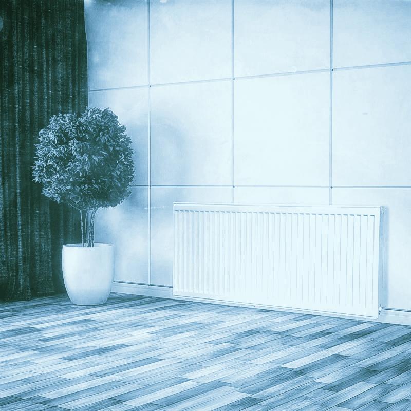 radiátor falra szerelve padlós szobában növény mellett