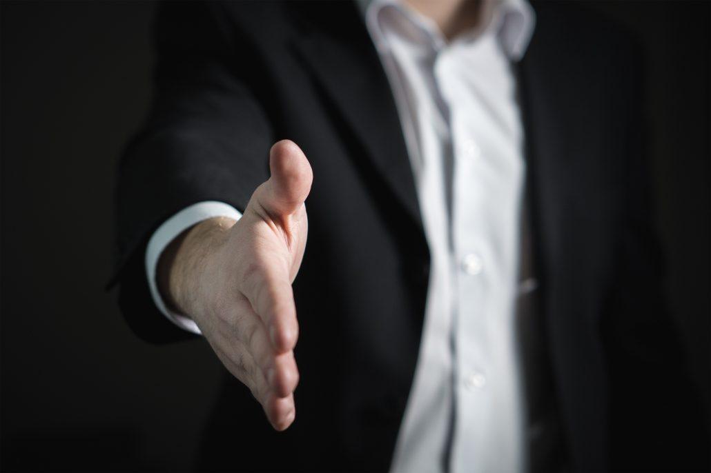 öltönyös férfi nyújtja a kezét üdvözlés képen