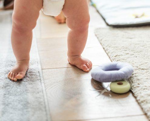 kisbaba meztelen lábbal a padlófűtésen áll