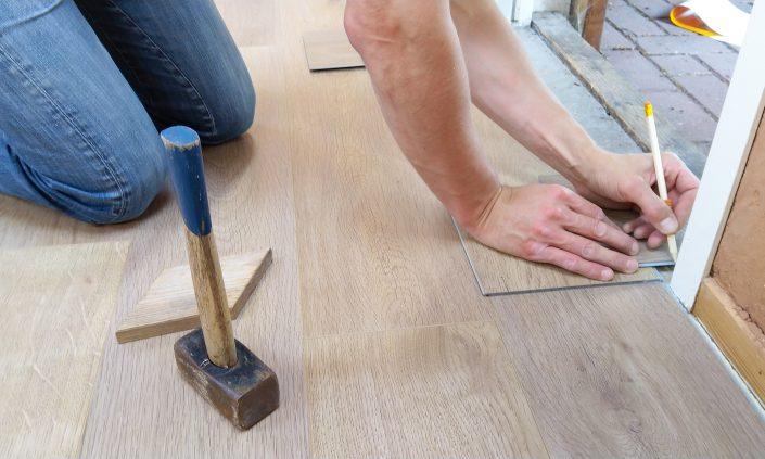 padlófűtést fednek le padlóval egy munkás éppen beszabja a lecet
