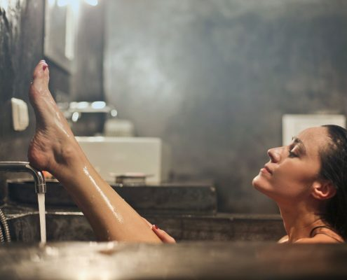 meleg fürdőszobában fekszik egy nő egy kádban