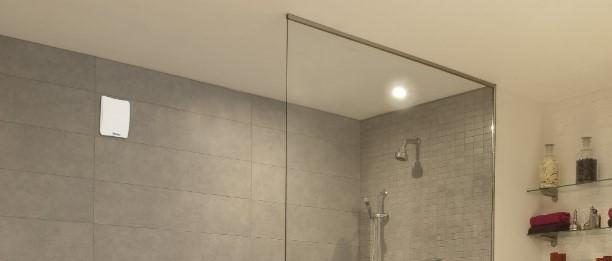 ventilátor a falon egy modern zuhanyzós fürdőszobában